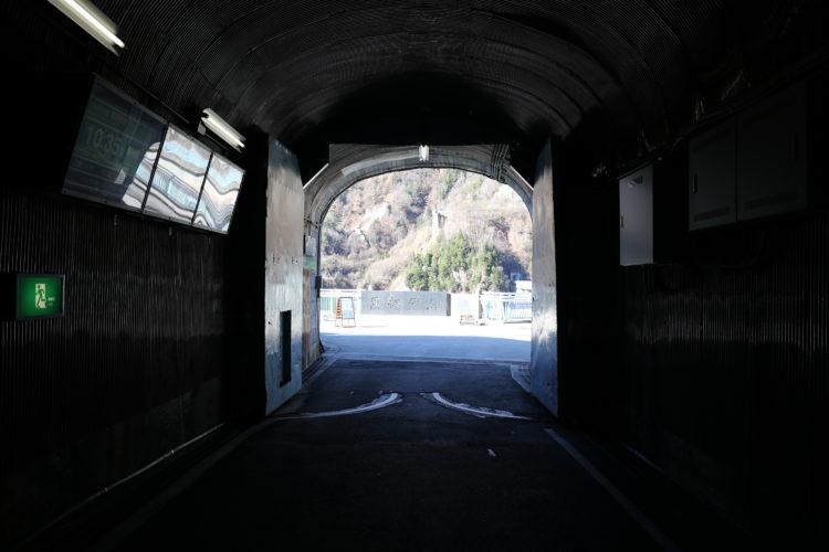 関電トロリーバス黒部ダム駅出口と黒部ダム記念碑